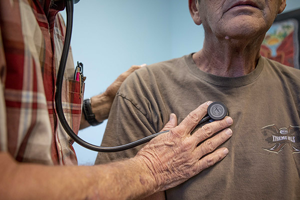 A doctor listens to a man's heart beat at a clinic in Bieber, California on July 23, 2019. Photo by Anne Wernikoff for CalMatters