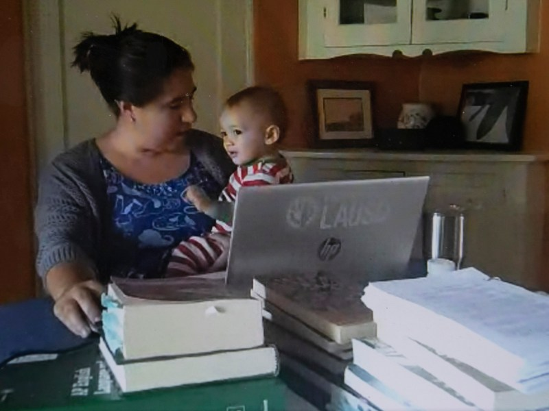 Maya Suzuki Daniels sits with her 14-month-old at the table where she teaches high school English. Daniel's expects that her son will make frequent appearances during her zoom lectures. Photo by Anne Wernikoff for CalMatters via Google Hangout