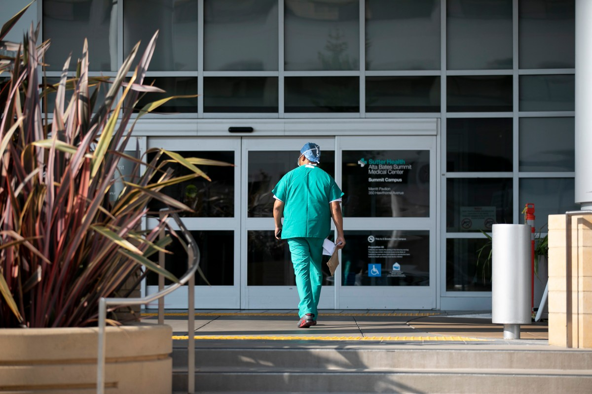 A hospital employee enters Alta Bates Summit Medical Center in Oakland on August 24, 2020. Photo by Anne Wernikoff for CalMatters