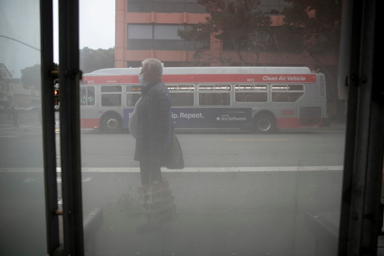 A rider waits for the 44 bus on Geary Blvd in San Francisco on Aug. 27, 2020. San Francisco eliminated all but 17 bus routes in April and risks permanently losing 40 of the original 68 lines running before the pandemic. Photo by Anne Wernikoff for CalMatters
