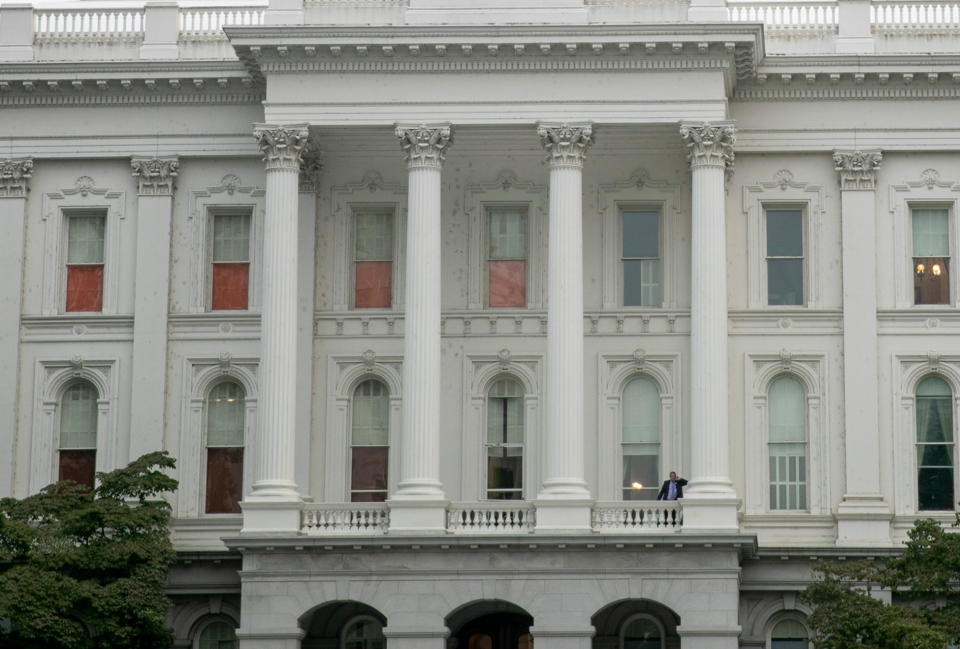 A man steps outside to take a phone call on the balcony of the capitol during the assembly recess on Aug. 31, 2020. Photo by Anne Wernikoff for CalMatters