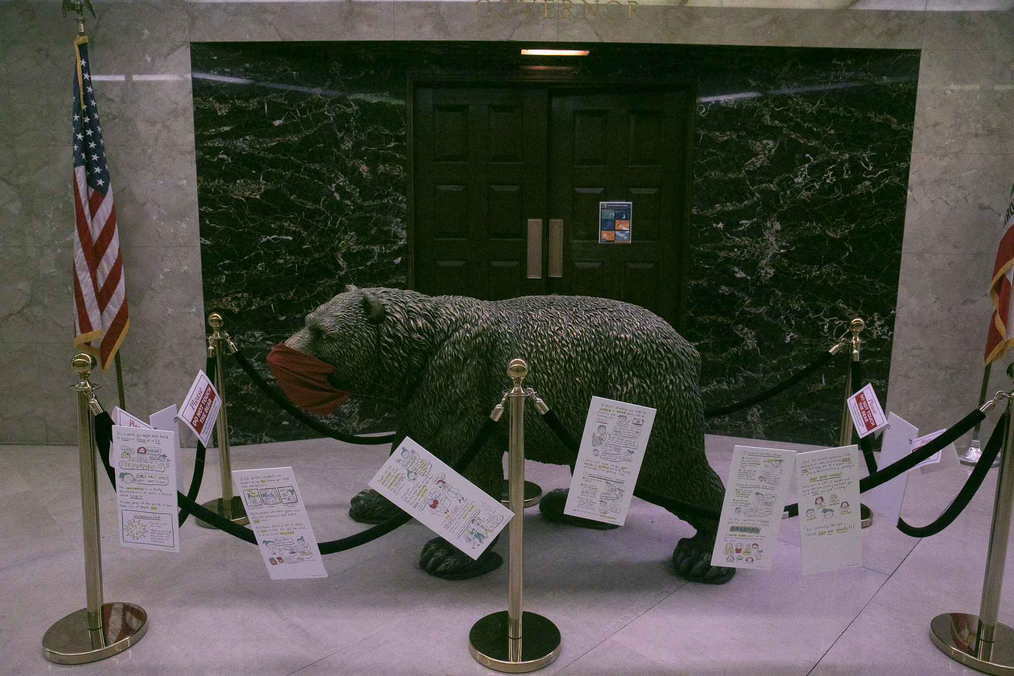 The beat statue in front of the governor's office sports a face mask and is surrounded by signs encouraging social distancing and hand washing on Aug. 31, 2020. Photo by Anne Wernikoff for CalMatters