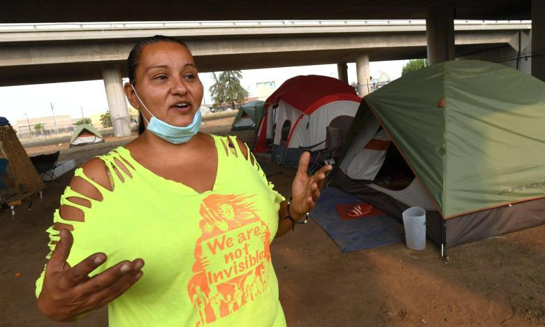 """Under Highway 41 in downtown Fresno, homeless advocate Dez Martinez talks Thursday Aug. 20, 2020, about the encampment she set up, named """"Dream Camp†by residents, to give homeless a safe and clean alternative to living on the streets. Photo by John Walker, The Fresno Bee"""