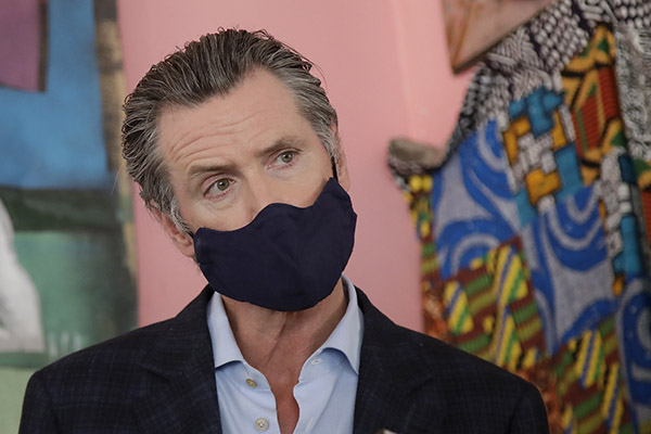 Gov. Gavin Newsom wears a protective mask on his face while speaking to reporters at Miss Ollie's restaurant during the coronavirus outbreak in Oakland, June 9, 2020. Photo by Jeff Chiu, AP Photo/Pool