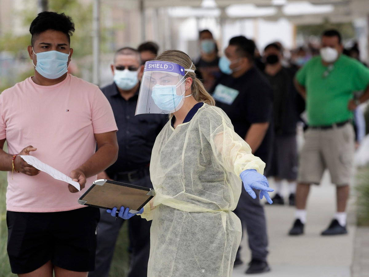 People line up behind a health care worker at a mobile coronavirus testing site at the Charles Drew University of Medicine and Science in Los Angeles on July 22, 2020. A technical problem has caused a lag in California's tally of coronavirus test results, casting doubt on the accuracy of recent data showing improvements in the infection rate and number of positive cases, and hindering efforts to track the spread, the state's top health official said today. Photo by Marcio Jose Sanchez, AP Photo