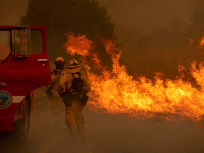 Firefighters attempt to stop a grass fire from jumping a road in Vacaville on Aug. 19, 2020. Firefighters across the state continue to battle against 560 fires, which have burned an area equivalent to the state of Rhode Island. Photo by Karl Mondon, Bay Area News Group
