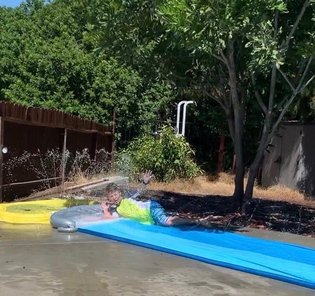 Assemblymember Gonzalez's 9-year-old son on the backyard Slip n' Slide.