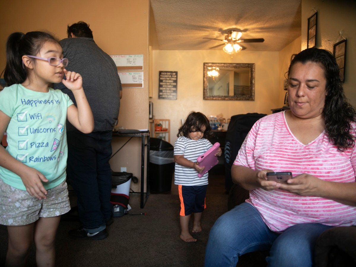 Mariana with her daughter Genessis, 8, and son Gerardo, 2, while her husband, Gerardo Hector prepared to leave for work on September 7, 2020. The family of four shares a one-bedroom apartment in National City but have fallen behind on rent payment due to Mariana and her husband both losing months of work amid the pandemic. Photo by Anne Wernikoff for CalMatters