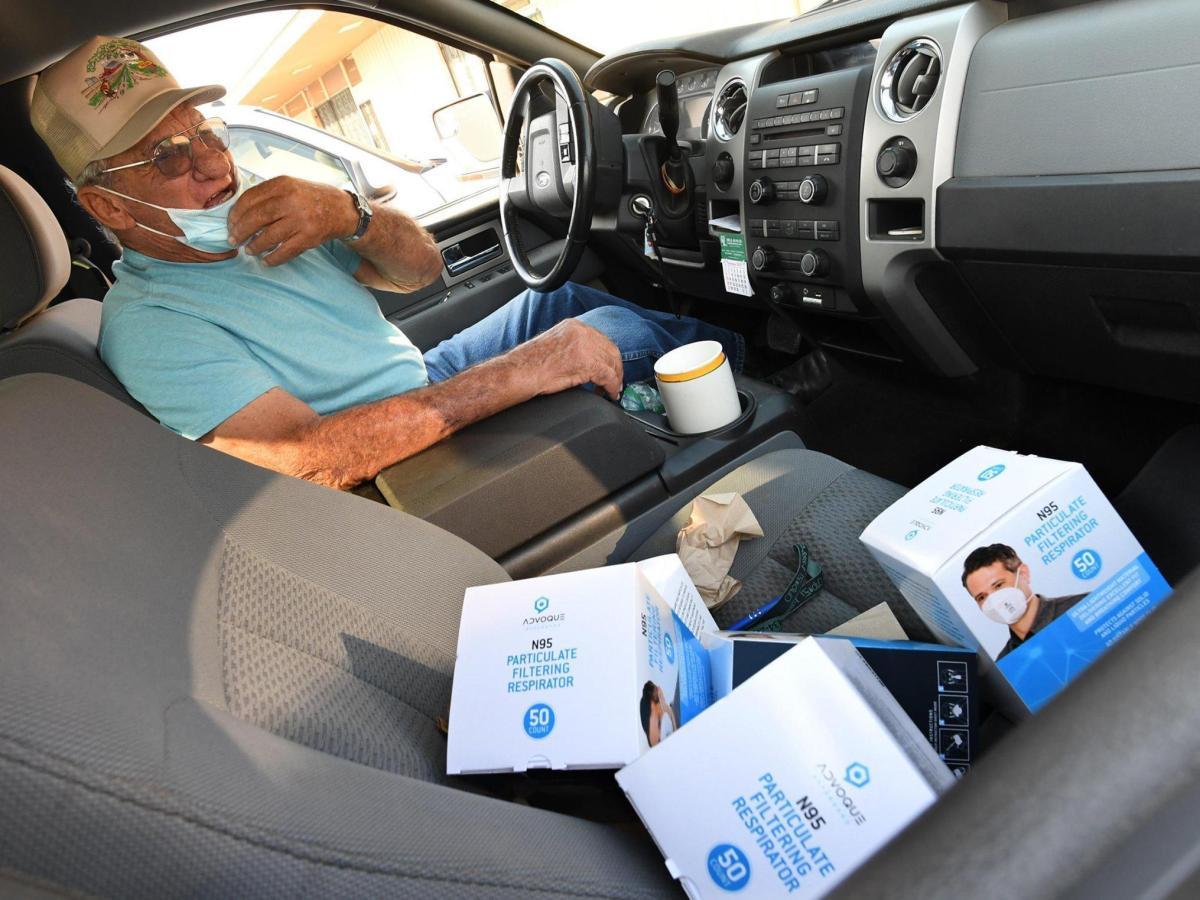 Alvin Rocca, de 82 años, agricultor de la zona de Fresno desde hace muchos años, agradece a un empleado de la Oficina Agrícola del Condado de Fresno por un suministro de mascarillas faciales N95 que se entregarán a sus trabajadores de campo, durante un evento de distribución de mascarillas en la oficina, llevado a cabo en la mañana del viernes 4 de septiembre de 2020. La seguridad de los trabajadores agrícolas es una prioridad, ya que se han entregado más de 300,000 mascarillas N95 a la comunidad agrícola en dos semanas, según el director general de la Oficina Agrícola del Condado de Fresno, Ryan Jacobson. Fotos de John Walker/The Fresno Bee.