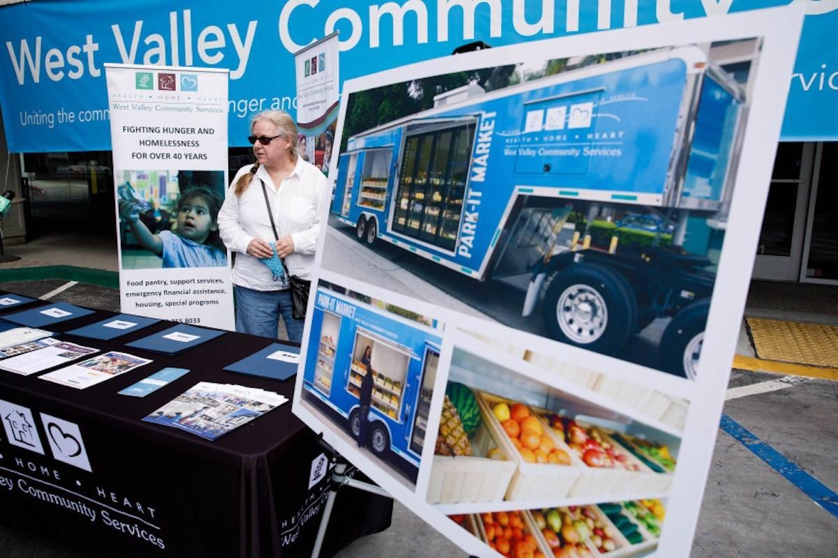 CUPERTINO - 16 DE SEPTIEMBRE: Gayelynn Miller, en el centro, está parada entre los dos carteles de la inauguración del nuevo establecimiento de West Valley Community Services en Cupertino, Calif., el miércoles 16 de septiembre de 2020. (Randy Vazquez/ Bay Area News Group)