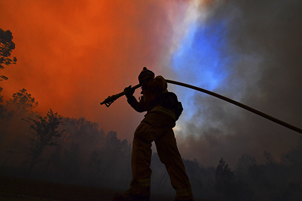 A firefighter pulls a hose while protecting a home along Crystal Springs Road while battling the Glass Fire in St. Helena on Sept. 26, 2020. Photo by Jose Carlos Fajardo, Bay Area News Group