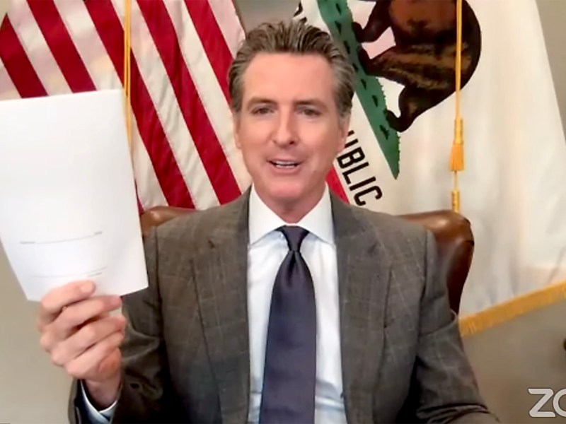 Gov. Gavin Newsom holds up a bill before signing it into law over zoom on Sept. 17, 2020. Screenshot via YouTube