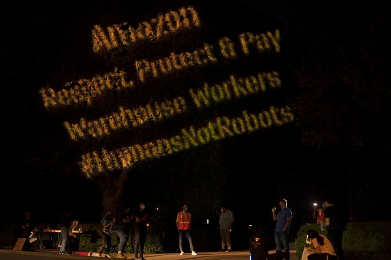"""Protestors project the words """"Amazon respect, protect and pay warehouse workers #humansnotrobots"""" onto the shrubs outside Amazon CEO, Jeff Bezos' house during a Prime Day protest . Oct. 13, 2020.Photo by Tash Kimmell for CalMatters."""