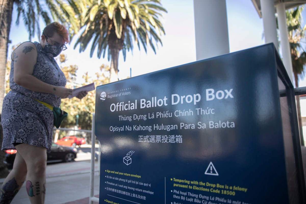 A voter deposits her ballot at an official box at Emeryville City Hall on Oct. 15, 2020. The California GOP has run afoul of Democratic state elections officials for placing its own boxes in or outside of gun shops, churches and other spots. Photo by Anne Wernikoff for CalMatters