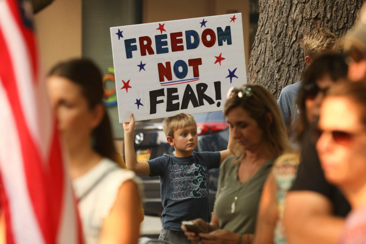 """Johnny Grandstaff, 8, of Durham Elementary, holds up a sign he made with his mom, saying, """"Freedom not fear!"""" in Chico, during a rally demanding that Butte County reopen on Oct. 2, 2020. Photo by Carin Dorghalli, Enterprise-Record"""