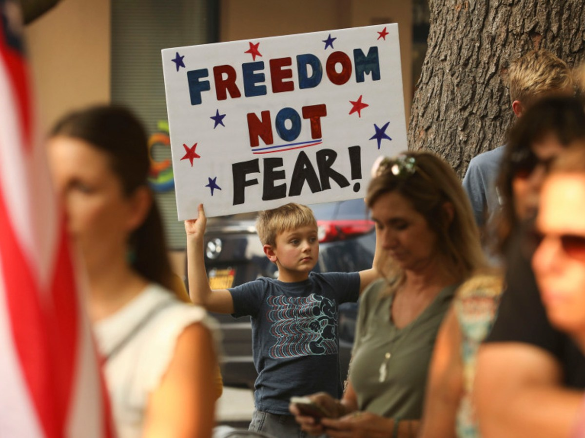 "Johnny Grandstaff, 8, of Durham Elementary, holds up a sign he made with his mom, saying, ""Freedom not fear!"" in Chico, during a rally demanding that Butte County reopen on Oct. 2, 2020. Photo by Carin Dorghalli, Enterprise-Record"