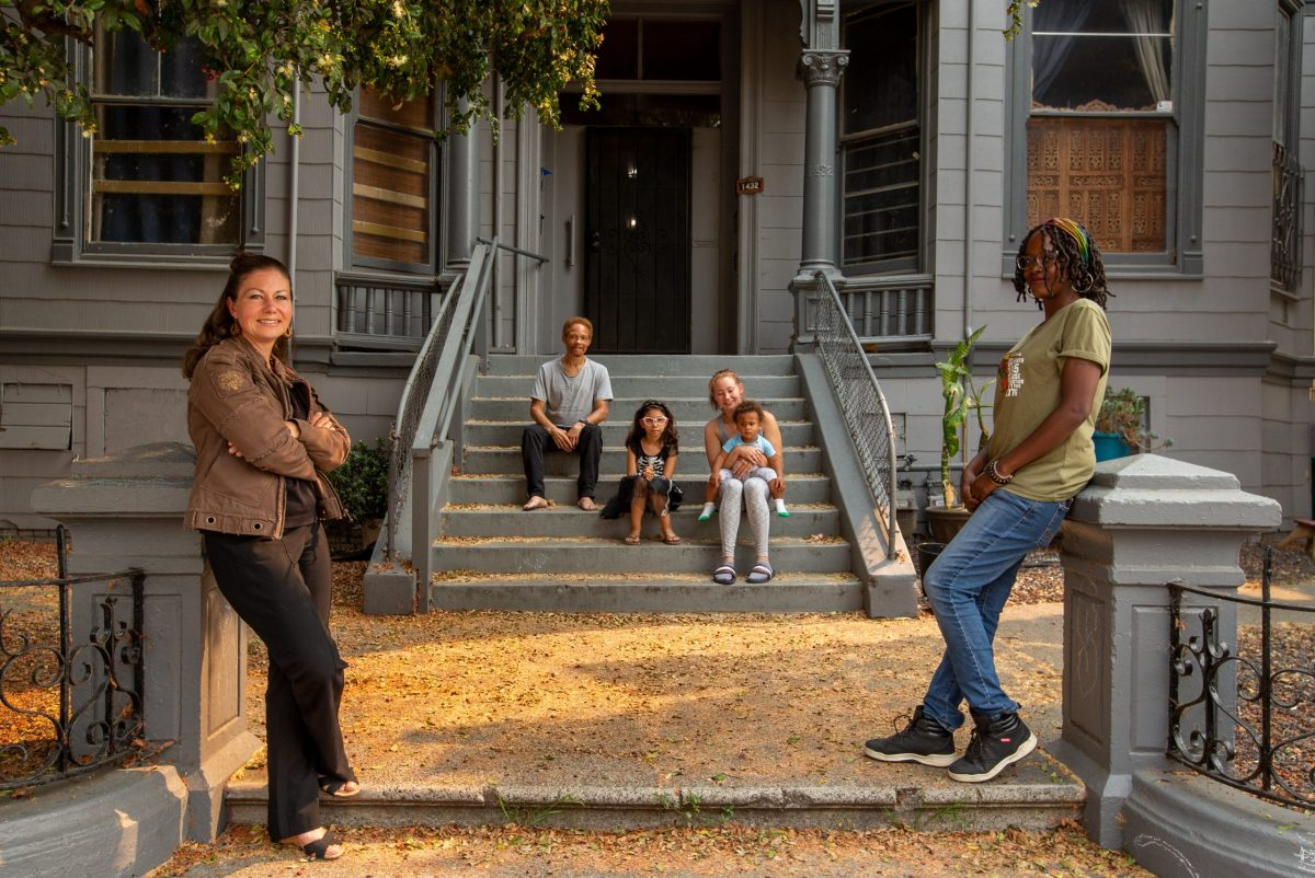 Christine Hernandez, left, Jayda Garlipp, right, pose for a photo in front of their home in Oakland, on Thursday, Oct. 1, 2020. Hernandez with her family of four moved into the apartment building without signing a lease two years ago. With the help of the Bay Area Community Land Trust, they bought the property. Now she is on her way to becoming a radical real estate lawyer. Photo by Ray Chavez, Bay Area News Group
