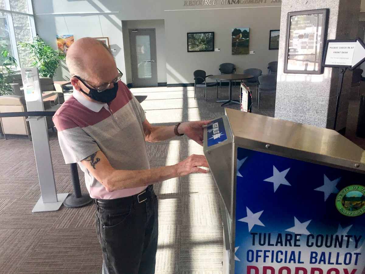 Jack Van Rooy places his mail-in ballot envelope into an official drop box in Visalia on Oct. 19, 2020. Photo by Lewis Griswold for CalMatters.