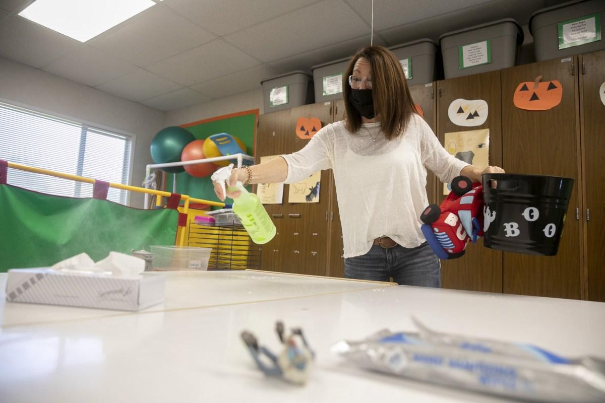 La instructora de educación especial Liz Duffield rocía las mesas en su salón de pre-kínder y jardín de infantes al final del día escolar el 27 de octubre de 2020. Duffield dice que la desinfección y la lavada de manos se han convertido en una parte importante para mantener a ella y a sus estudiantes saludables y tiene la intención de continuar con ellos después de la pandemia. Foto de Anne Wernikoff para CalMatters