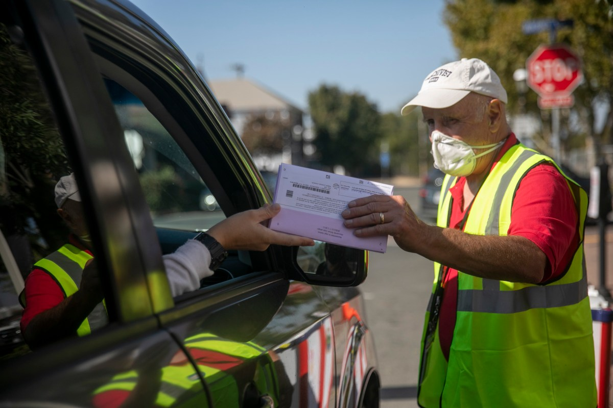 Jerry Handfield collects ballots at a drive-thru voting location in front of the Contra Costa County clerk-recorder office in Martinez on Oct. 31, 2020. Photo by Anne Wernikoff for CalMatters