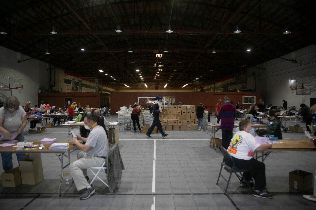 Dozens of volunteers extract ballots at the sports complex in Martinez on Oct. 31, 2020. By Halloween, Contra Costa County had already received more ballots than the total number in the March primary. Photo by Anne Wernikoff for CalMatters