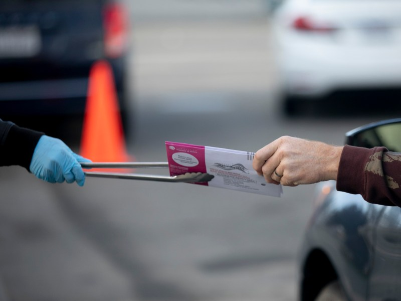 Poll workers use tongs to collect ballots and hand out stickers at a curbside voting location at Alameda County courthouse on Nov. 3, 2020. Photo by Anne Wernikoff for CalMatters