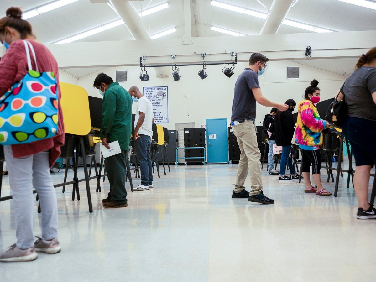 Volunteer poll worker David Saunders helps a voter at a Los Angeles Elementary School polling place on Election Day. Early California results provided some answers but remaining questions. Photo by Tash Kimmell for CalMatters