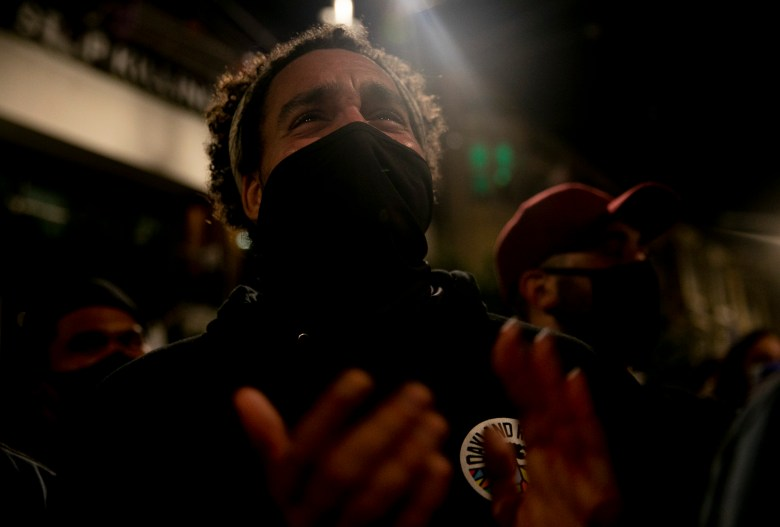 """Oakland resident Kaleb Lawson becomes emotional on San Francisco's Castro Street as he watches President-elect Joe Biden's televised victory speech. """"We have a woman as VP,"""" said Lawson. """"And she's a Black woman after these four years. I can't even say that without tearing up."""" Photo by Anne Wernikoff for CalMatters"""