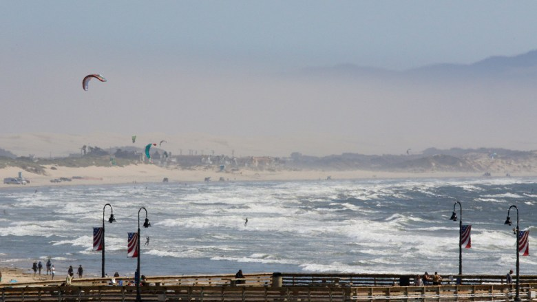 Wind and a dusty haze obscure the view of coastal hills from south of the Pismo Pier on August 21, 2019. That day, the average level of particulate pollution in the air was twice the level considered to be unhealthy by the World Health Organization. Photo by David Middlecamp, San Luis Obispo Tribune