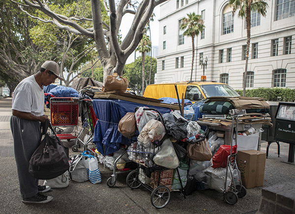 Esteban Gonzalez keeps watch over a dozen shopping carts full of personal items belonging to a group of homeless individuals across the street from Los Angeles City Hall on August 7, 2019. According to Gonzalez, someone must stay with the shopping carts at all times to avoid having their items taken away by authorities so he and the other participants take turns throughout the day never leaving the carts unattended. Photo by Anne Wernikoff for CalMatters