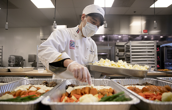 Advanced cuisine student Soon Gi Hwang places butter pats into trays of prepared thanksgiving dinners which will be frozen and distributed through the campus food pantry at Diablo Valley College on Nov. 18, 2020. Photo by Anne Wernikoff for CalMatters