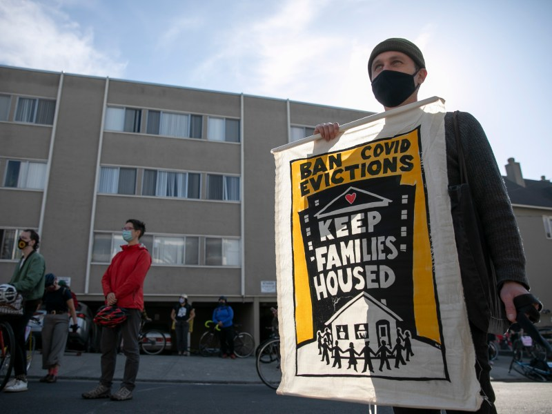 Oakland resident Andrew Rosenburg holds up a banner while protesting rent evictions during the pandemic on Dec. 5, 2020 in Oakland. Photo by Anne Wernikoff for CalMatters