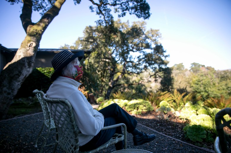 Lucy Smallreed sits in the garden at her home in Inverness on Dec. 6, 2020. Smallreed remains vigilant about cutting back the trees and bushes on her property but is unable to qualify for insurance. Photo by Anne Wernikoff for CalMatters