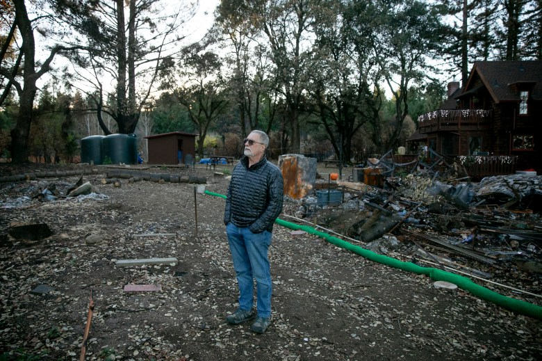 Lad Wallace in front of his home in Bonnie Doon on Dec. 15, 2020. Wallace's home survived the CZU Lightening Complex Fires in August but he lost his garage, seen behind Wallace, and many trees on his property were killed. Photo by Anne Wernikoff for CalMatters
