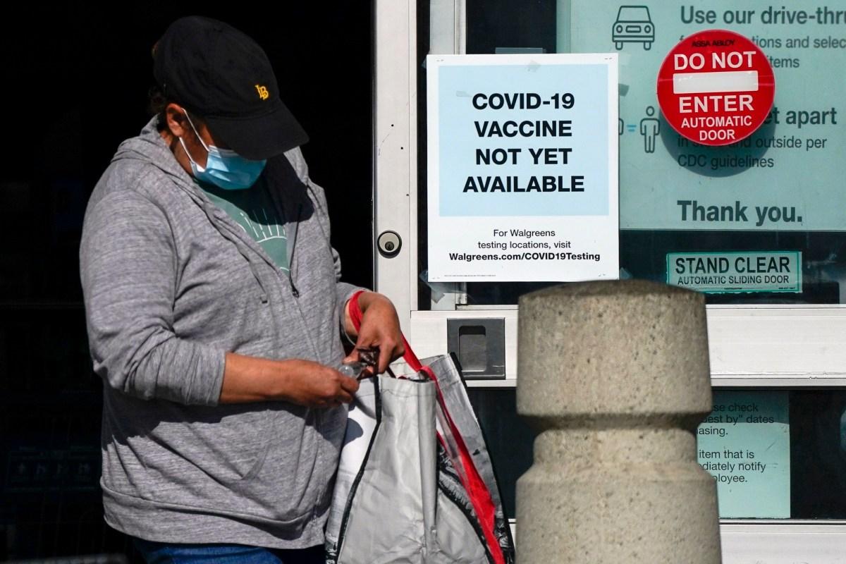 Un cliente pasa junto a un letrero que indica que la vacuna COVID-19 aún no está disponible en Walgreens el 2 de diciembre de 2020 en Long Beach. Foto de Ashley Landis, AP Foto