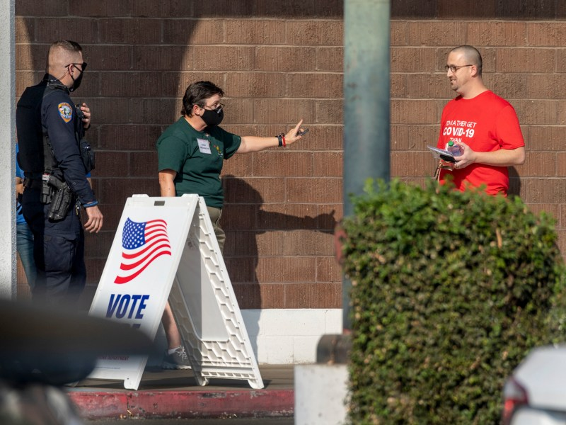 Cheri Provancha, center, denies Christopher Rickman access to the polling place at the old Sears building on November 3, 2020. He was told the shirt's wording violated federal electioneering law. Photo by Ron Holman, Visalia Times Delta