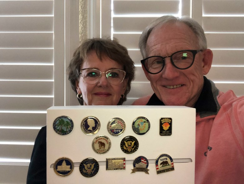 Jeannette and Mickey Logue hold up the commemorative pins they have received over the years for their service as poll workers. Photo courtesy of Jeannette Logue