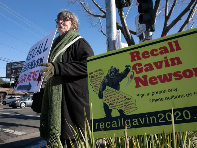 Recall Newsom volunteer Kerin Kay holds up a sign during a petition signing event at SaveMart in Sacramento on Jan. 5, 2021. Photo by Anne Wernikoff, CalMatters