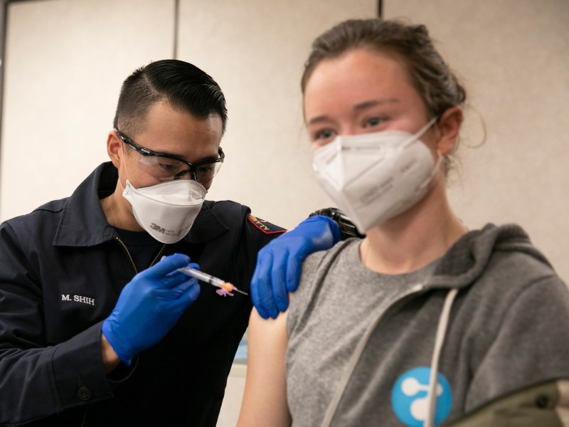 Alameda County Fire Department employee Max Shih, left, administers the second dose of the Moderna COVID-19 vaccine to Julia Jackson, a volunteer at a Berkeley needle exchange program, at St. Rose hospital in Hayward on Jan. 27, 2021. Photo by Anne Wernikoff, CalMatters