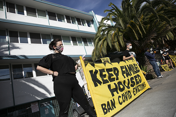 Demonstrators hold up a banner in front of an apartment building in the Adams Point neighborhood of Oakland to protest rent payment and evictions during the coronavirus pandemic on Dec. 5, 2020. Photo by Anne Wernikoff for CalMatters