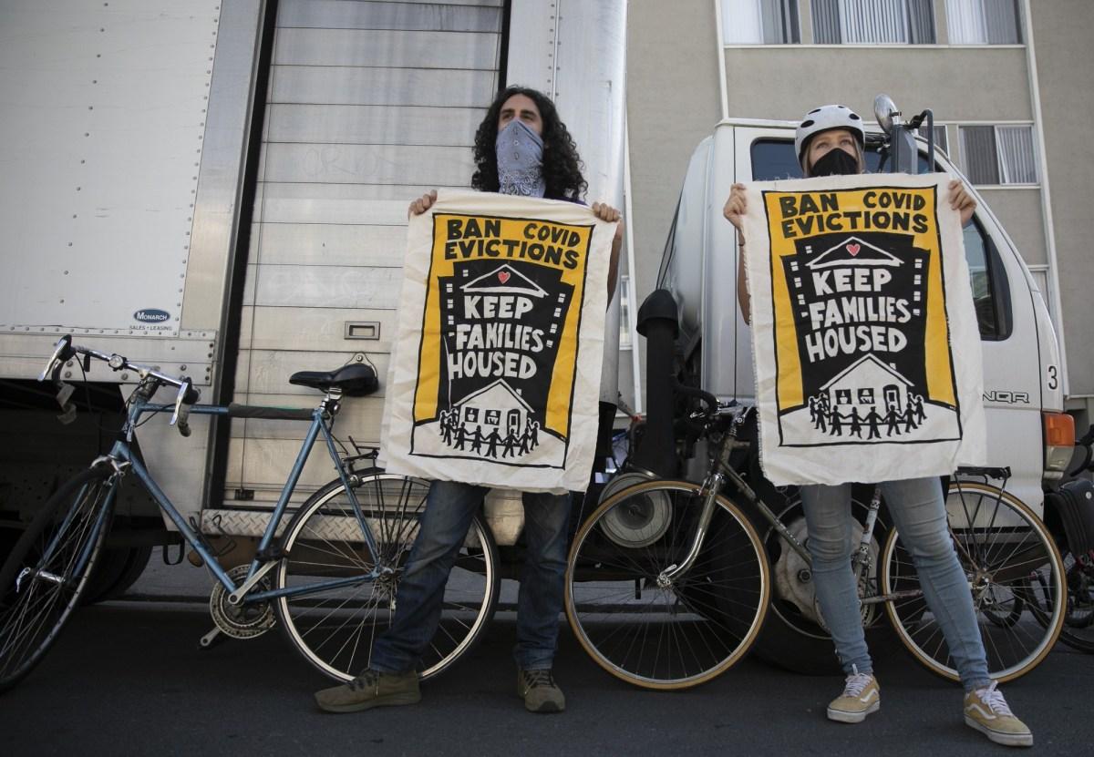 Galen Mancino, izquierda, y Betsy Kinsey, sostienen pancartas durante una manifestación de justicia de vivienda en el vecindario Adams Point de Oakland el 5 de diciembre de 2020. Foto de Anne Wernikoff para CalMatters