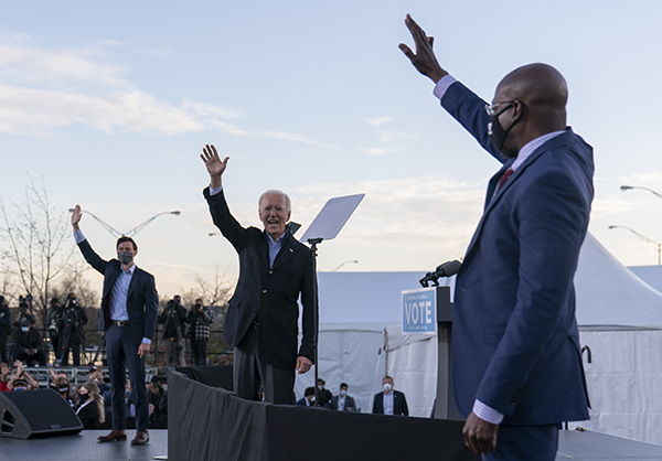 President-elect Joe Biden stands on stage with Raphael Warnock, right, and Jon Ossoff, left, who have both won U.S. Senate races to represent Georgia, in Atlanta, Jan. 4, 2021. Photo by Carolyn Kaster, AP Photo