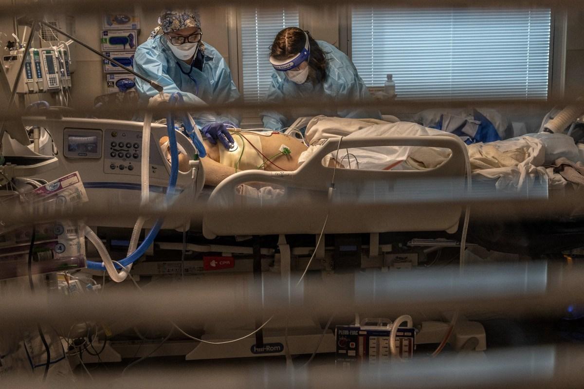 La asistente de laboratorio flebotomista Jennifer Cukati, a la derecha, y la enfermera registrada Carina Klescewski, a la izquierda, tratan a un paciente con COVID-19 dentro de la UCI del Centro Médico Sutter Roseville en Roseville el 22 de diciembre de 2020. California se convirtió en el primer estado en registrar 2 millones de casos confirmados de coronavirus, alcanzando el hito en la víspera de Navidad tan cerca que todo el estado estaba bajo una estricta orden de quedarse en casa y los hospitales se inundaron con la mayoría de los casos desde que comenzó la pandemia. Foto de Renee C. Byer, The Sacramento Bee vía AP / Pool