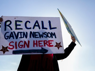 Recall Newsom volunteer Pat Miller holds up a sign during petition signing event at SaveMart in Sacramento on Jan. 5, 2021. Photo by Anne Wernikoff, CalMatters