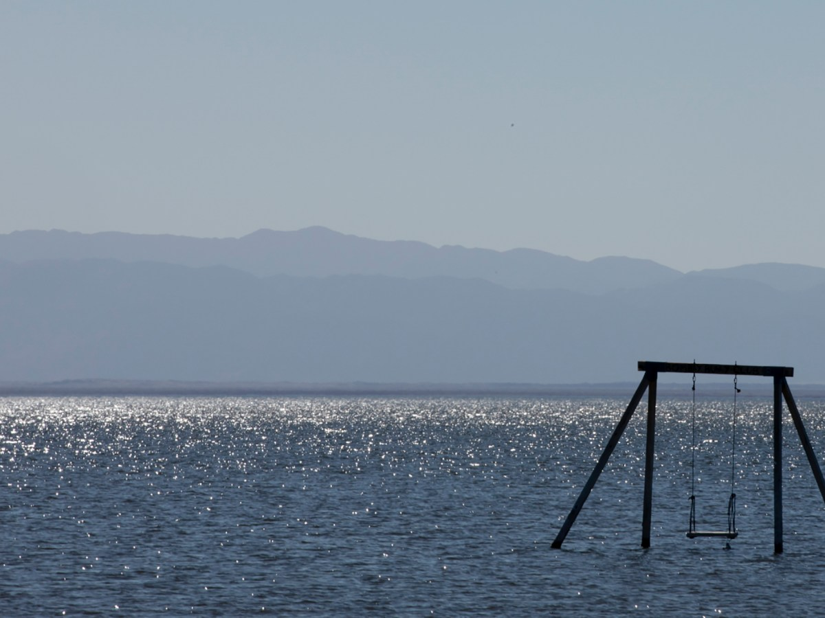 A swing set stands alone in the Salton Sea. State officials are helping fund experimental projects to extract valuable lithium from the lake's brine. Photo by Shae Hammond for CalMatters
