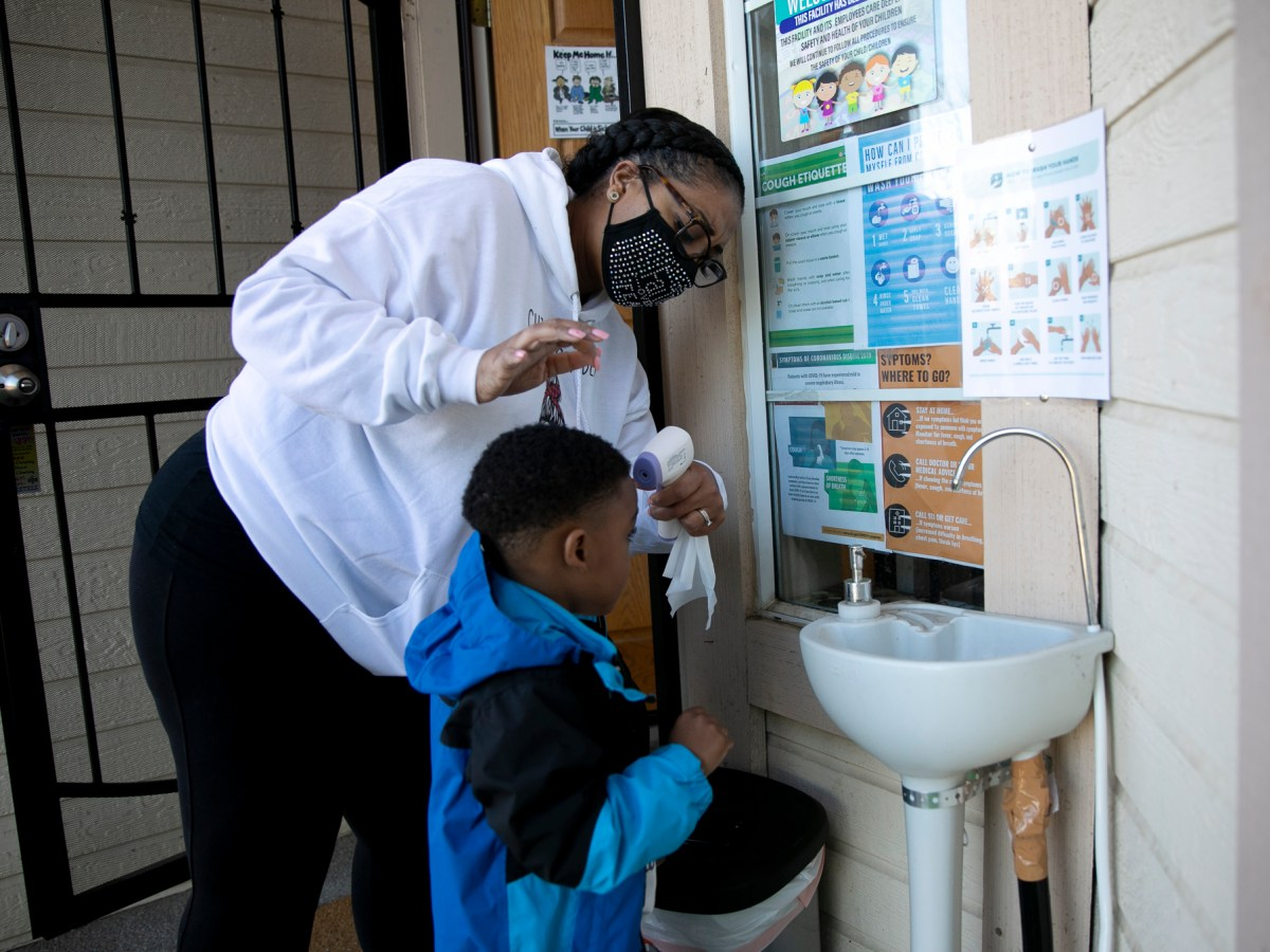 Family daycare provider Lucre-ce Lester takes a student's temperature as he arrives for the day at her home-based daycare in Antioch on Feb. 17, 2021. Photo by Anne Wernikoff, CalMatters