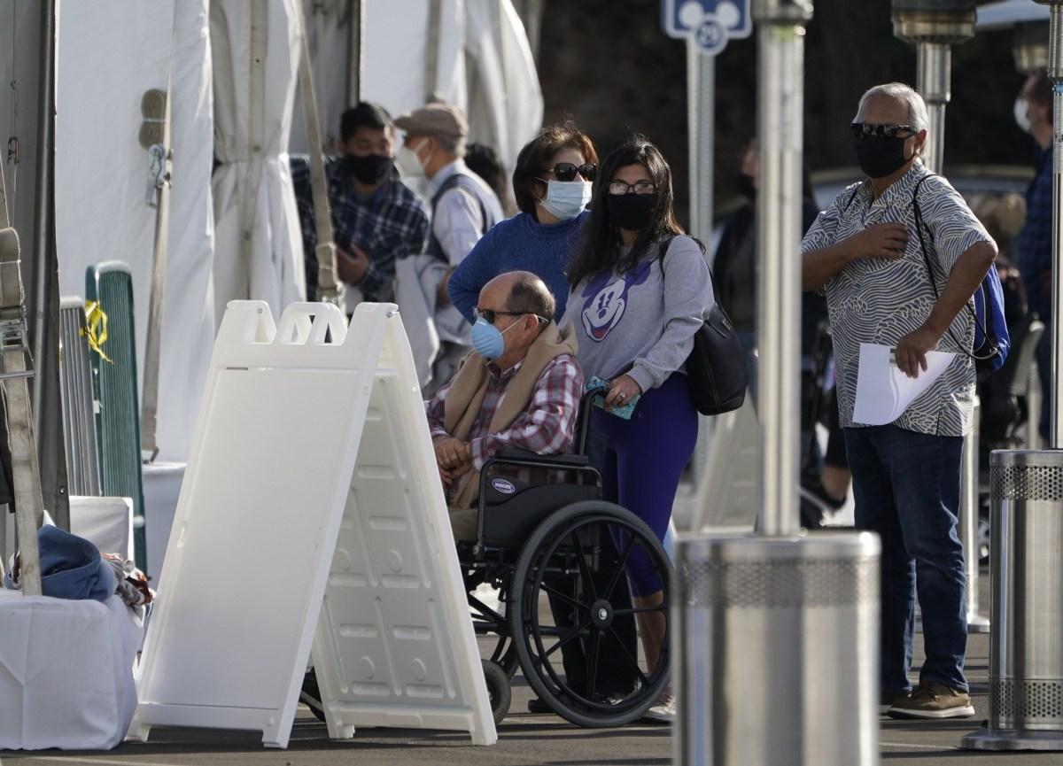 Los residentes del condado de Orange hacen fila afuera con carpas para recibir una vacuna COVID-19 en el Disneyland Resort en Anaheim el 13 de enero de 2021. Los defensores esperaban que un panel estatal le diera una mayor prioridad a la vacuna COVID a los californianos discapacitados. Foto de Damian Dovarganes, AP Foto