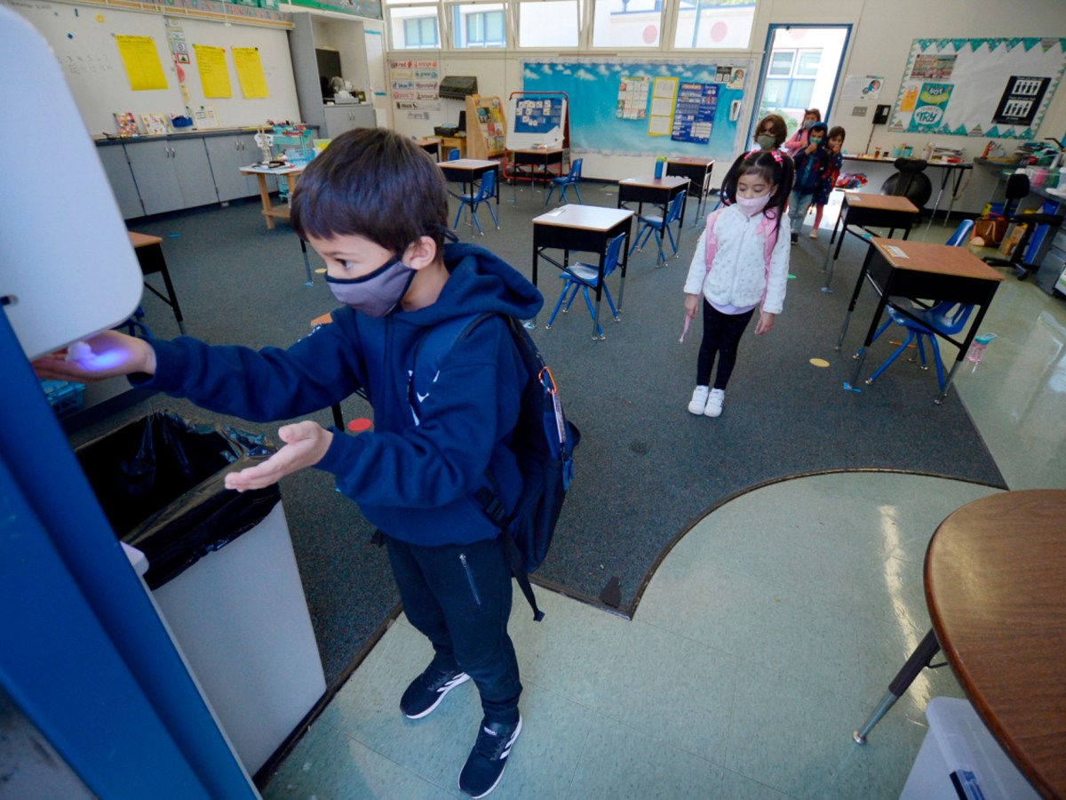Kindergarten student Nima Alipour uses the no-touch hand sanitize dispenser class at Sun Valley Elementary School in San Rafael on Nov. 10, 2020. Nearly all of Marin County schools have been open for in-person instruction since January. Photo by Sherry LaVars, Marin Independent Journal