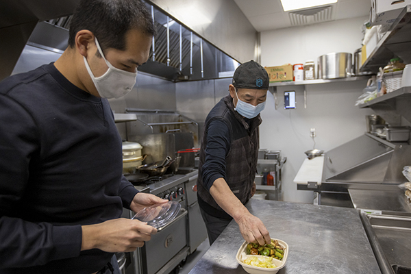 Dan Zhao, left, and father Keguang Zhao package up a Kung Pao Tofu at Cozy Wok, a vegetarian Chinese delivery and take-out restaurant, in Oakland on Jan. 28, 2021. Dan Zhao, a product manager at a San Francisco-based software company, and father Keguang Zhao opened up the restaurant, that is open nights and weekends, during the coronavirus pandemic. Photo by Anda Chu, Bay Area News Group