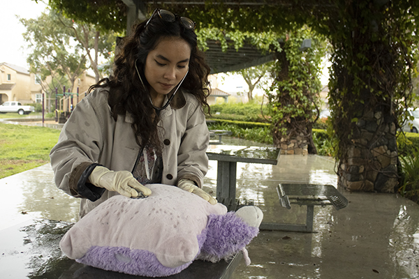 Nursing student Erin Abille demonstrates practicing nursing techniques on a stuffed animal at Mulberry Park in Chula Vista on January 23, 2021. Photo by Arlene Banuelos for CalMatters